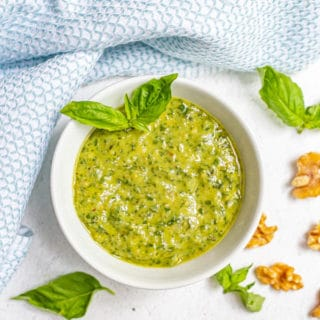 A white bowl of fresh basil pesto with sprigs of homemade pesto and walnut pieces scattered nearby
