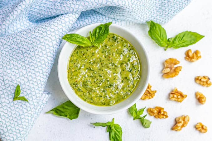 A white bowl of fresh basil pesto with sprigs of fresh pesto and walnut pieces scattered nearby