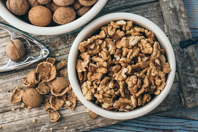 Shelled walnuts in a bowl beside a bowl of walnuts in the shell