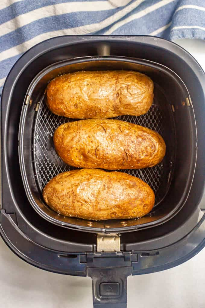 Three potatoes in an Air Fryer tray after cooking