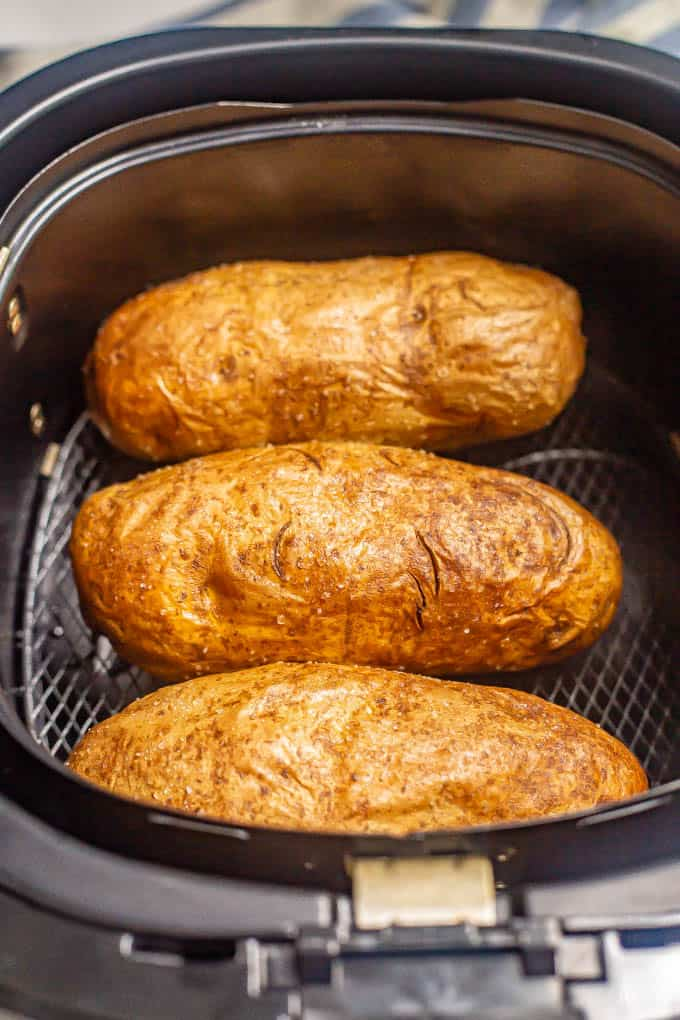 Three russet potatoes in an Air Fryer tray after cooking