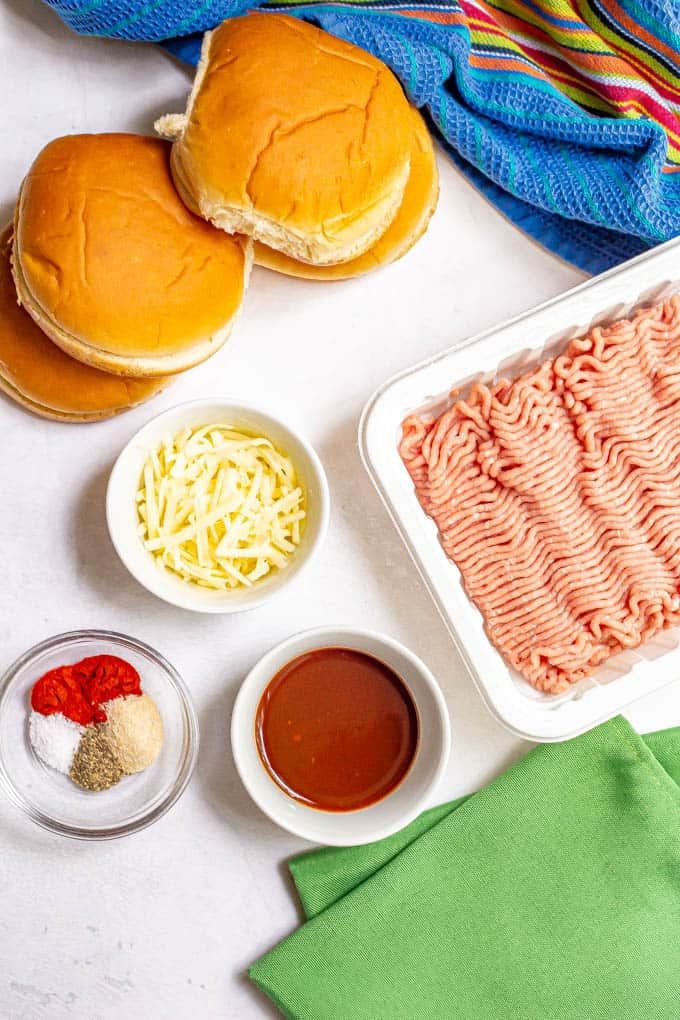 Ground turkey and other burger ingredients laid out on a white counter
