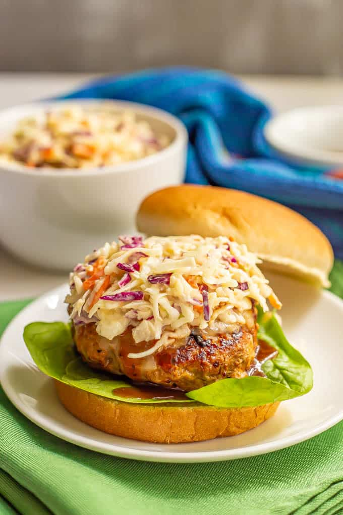 A coleslaw topped burger with BBQ sauce and lettuce and a bowl of coleslaw in the background