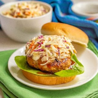 A turkey burger with coleslaw on a white plate on green napkins