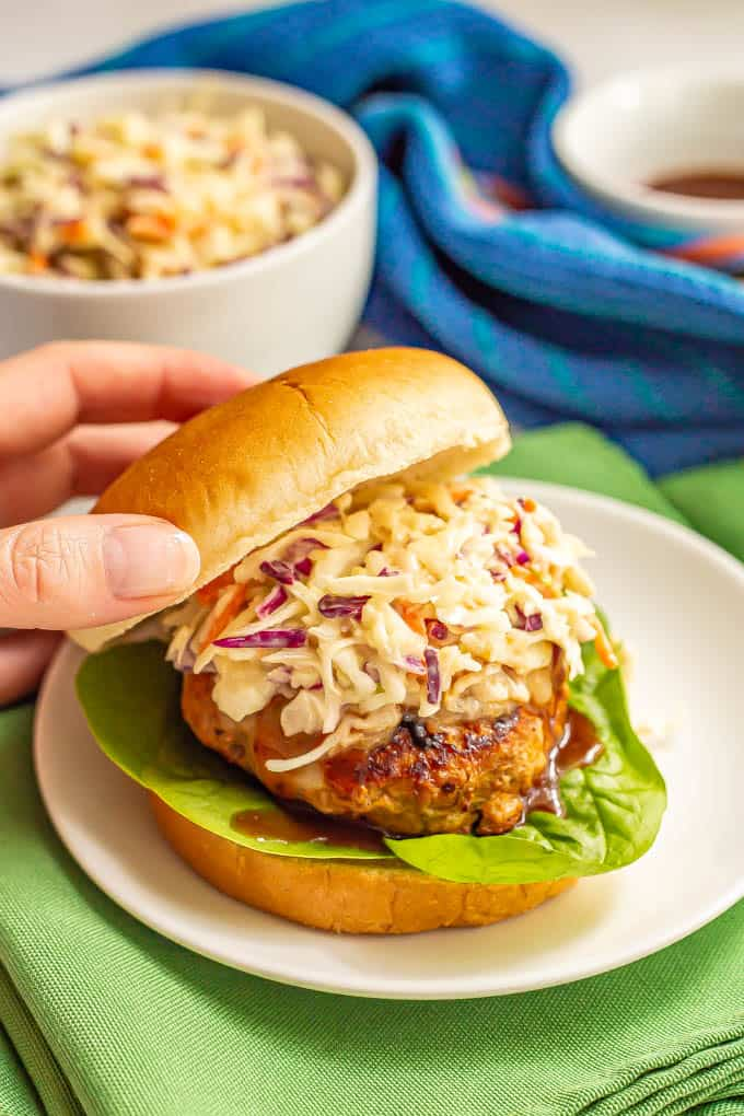 A burger bun top about to be placed on top of a BBQ turkey burger topped with slaw