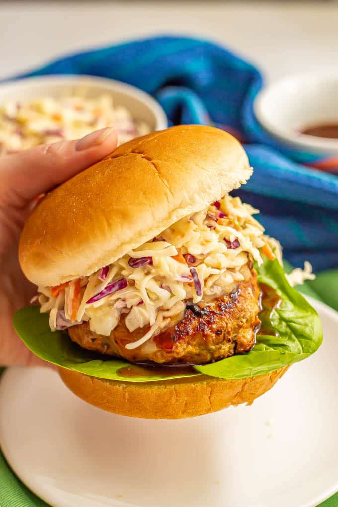 A hand picking up a turkey burger with coleslaw from a white plate