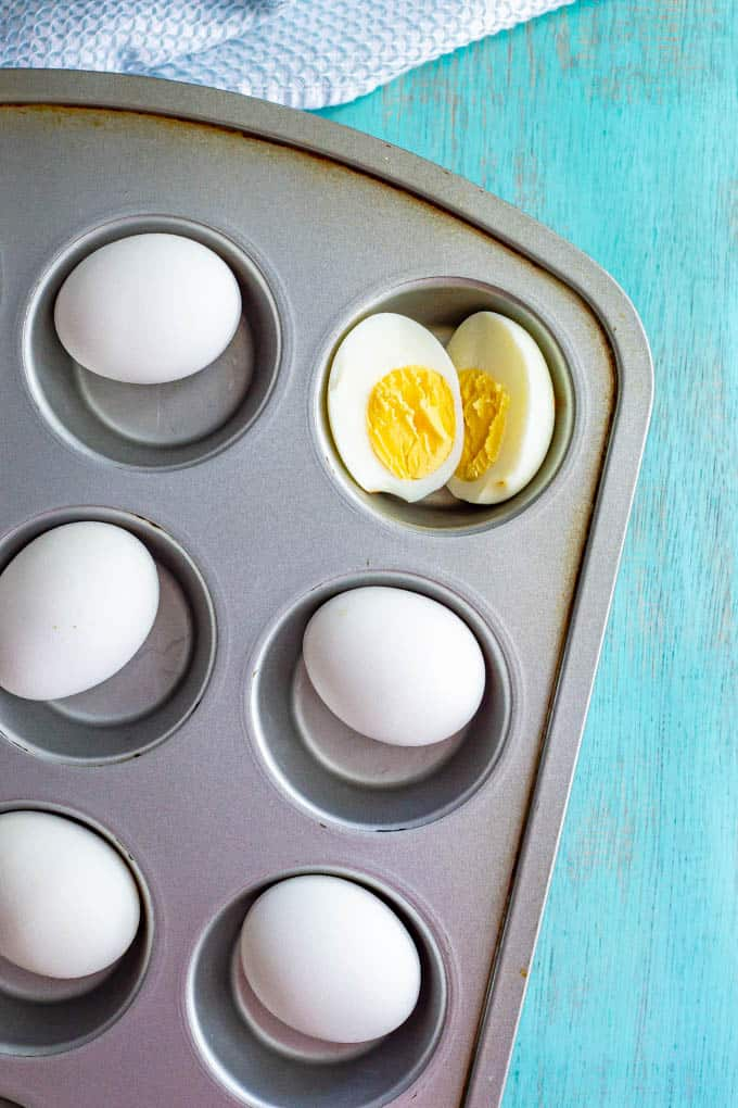 Eggs in a muffin tin with one hard boiled egg cut open in half