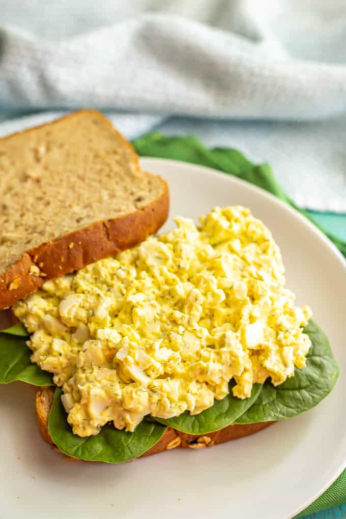 Egg salad piled on a bed of spinach on the bottom half of a sandwich