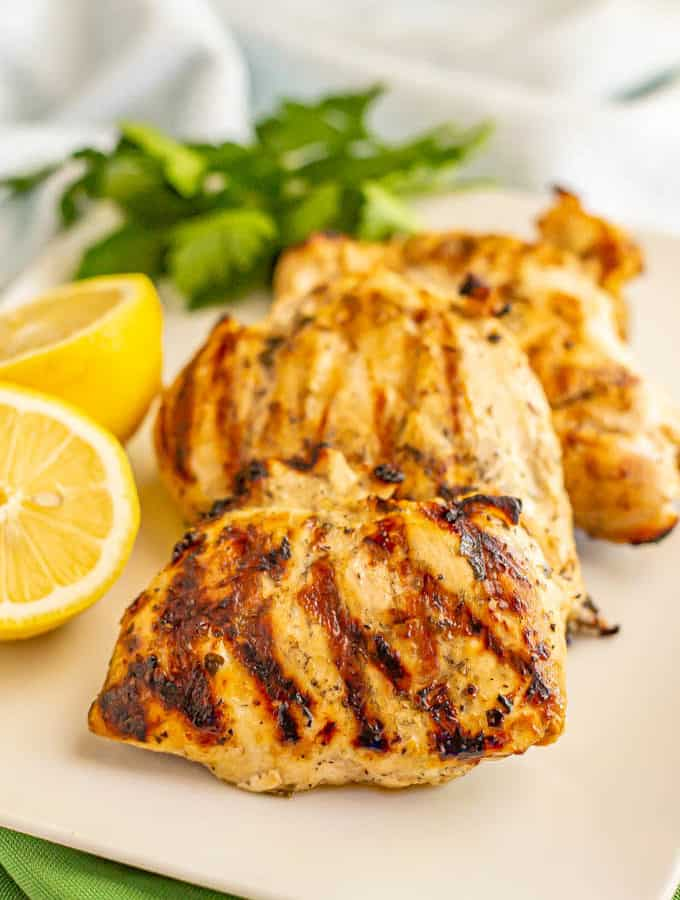 Grilled chicken breasts on a white serving platter with parsley and lemon as garnishes