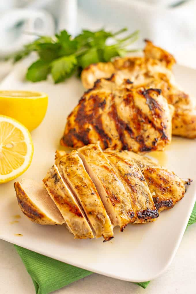 Grilled chicken breasts on a white serving platter with one sliced and with parsley and lemon as garnishes