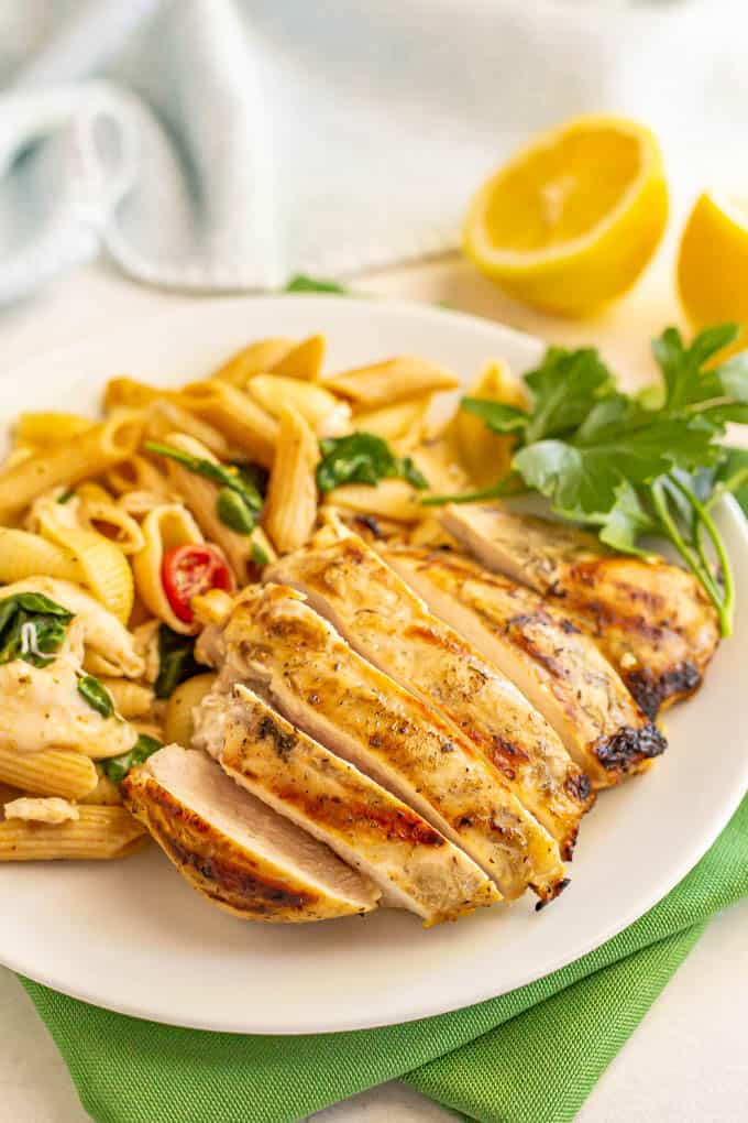 Sliced grilled chicken breast on a dinner plate with a pasta salad