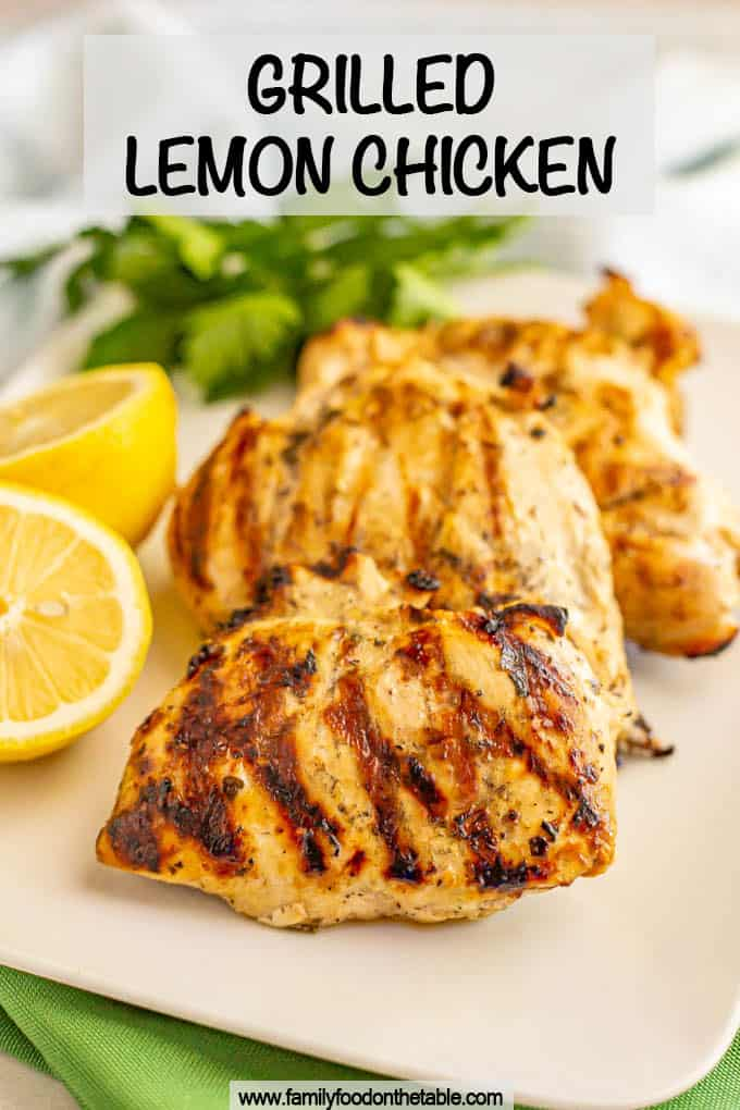 Grilled lemon chicken on a white serving platter with parsley and lemon as garnishes