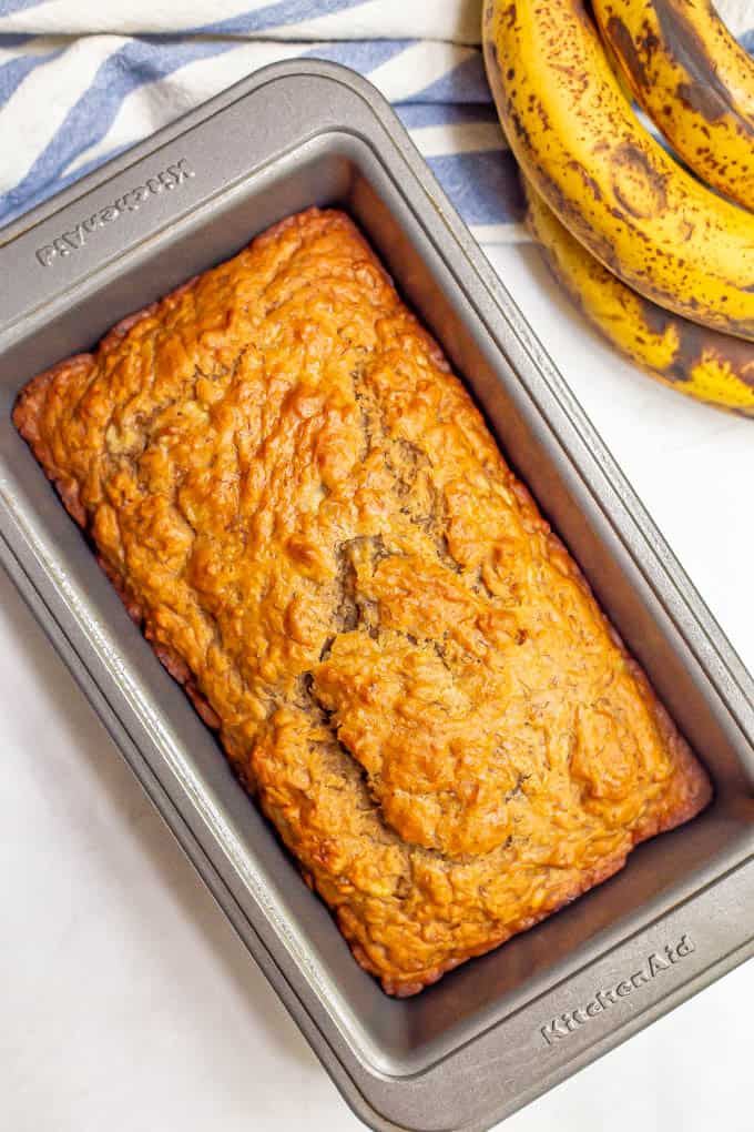 Golden brown whole wheat banana bread in a bread pan after baking