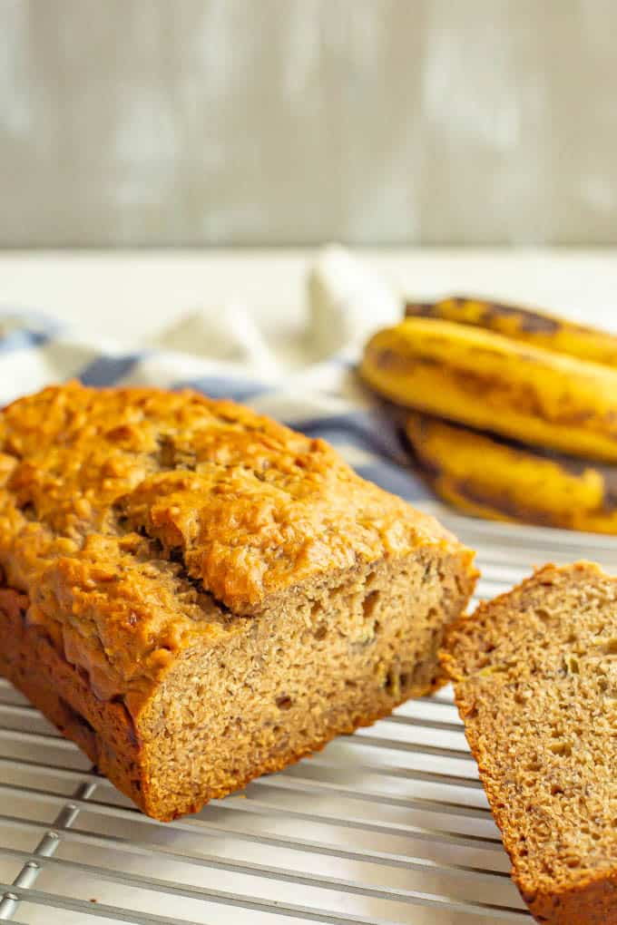 A loaf of banana bread on a cooling rack with slices cut out