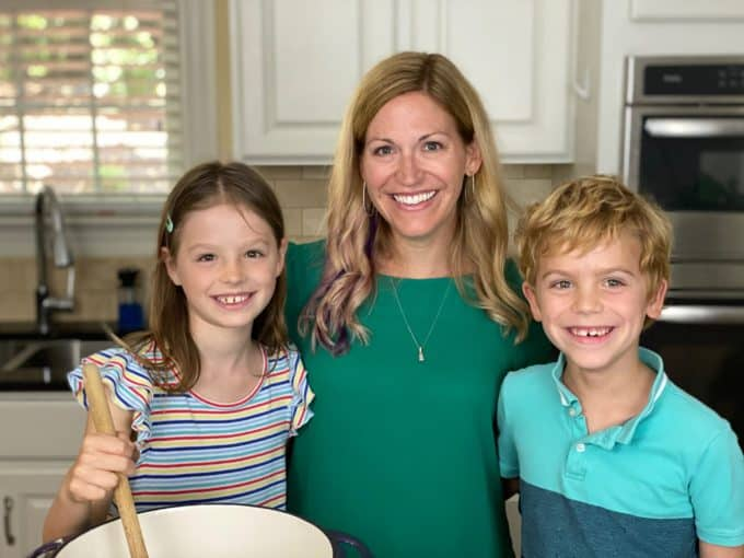 A mom and her two children cooking together in a kitchen