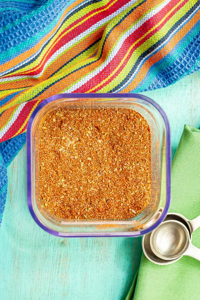 A square glass container filled with a homemade seasoning mix with measuring spoons resting nearby