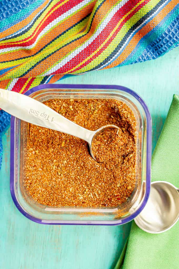 A teaspoon resting in a container of southwest seasoning