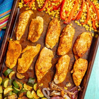 A baking sheet with cooked seasoned chicken strips and roasted vegetables