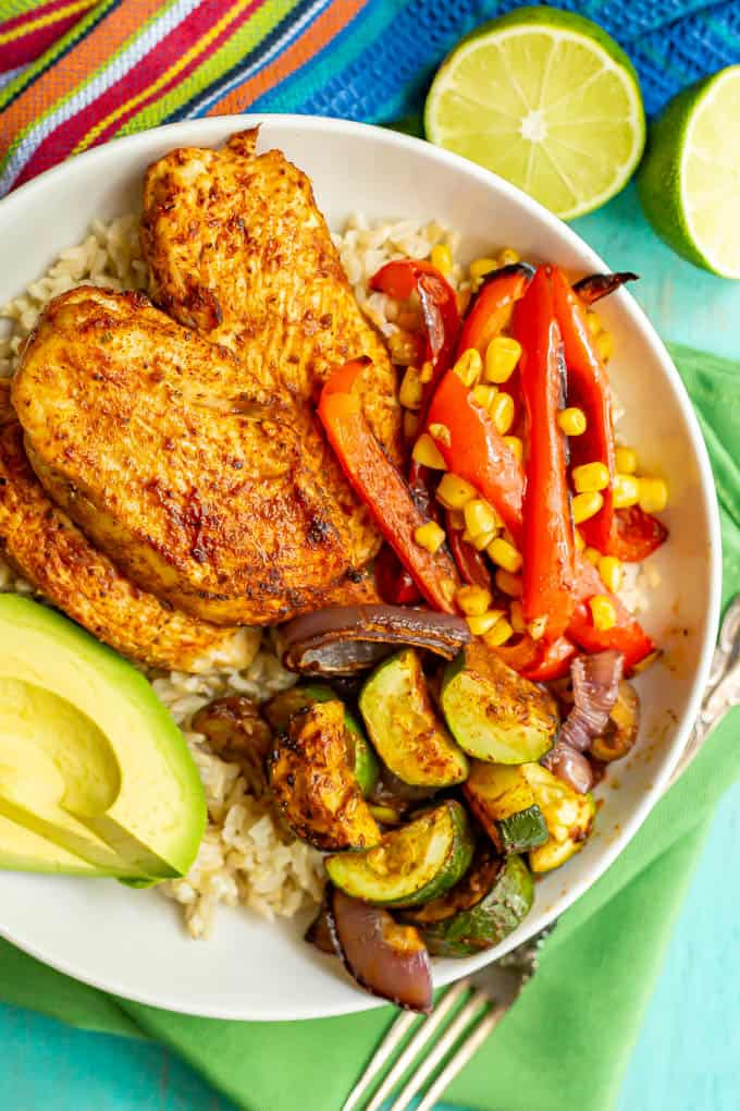 Southwest seasoned chicken and veggies served over rice in a large white bowl