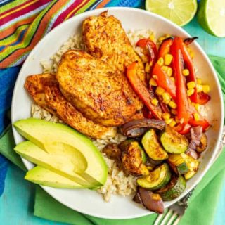 Roasted chicken and vegetables served over rice with avocado slices on the side