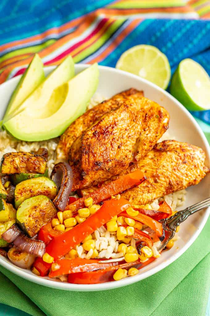 A fork tucked into a large white bowl of chicken and veggies over steamed brown rice