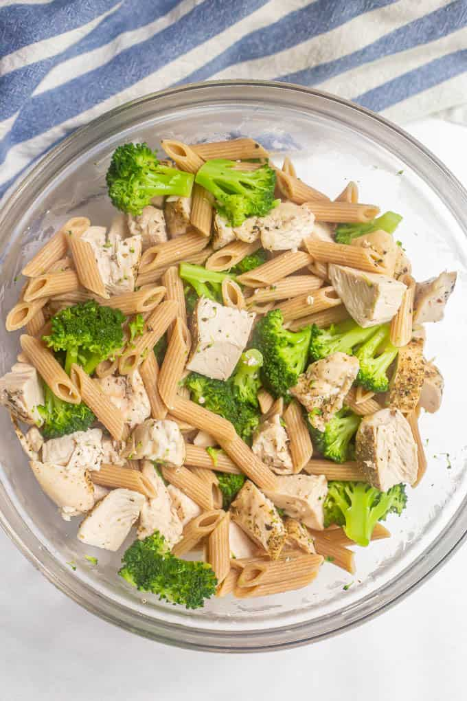 Pasta, cooked chicken and broccoli mixed together in a large glass bowl
