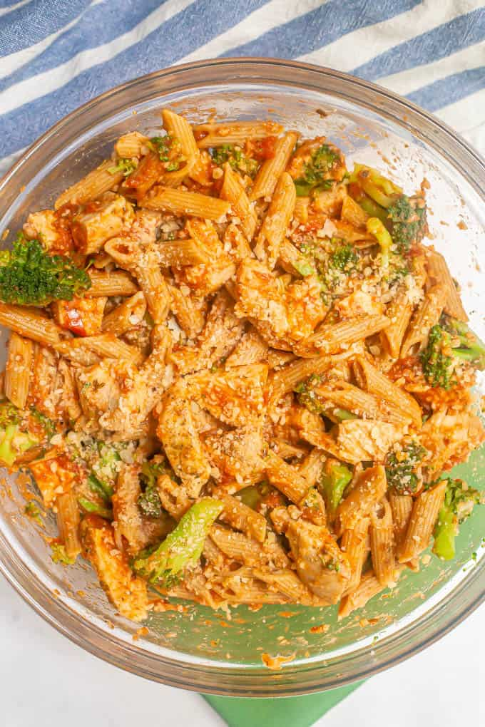 Large glass bowl of a pasta mixture with chicken, broccoli, marinara and Parmesan cheese