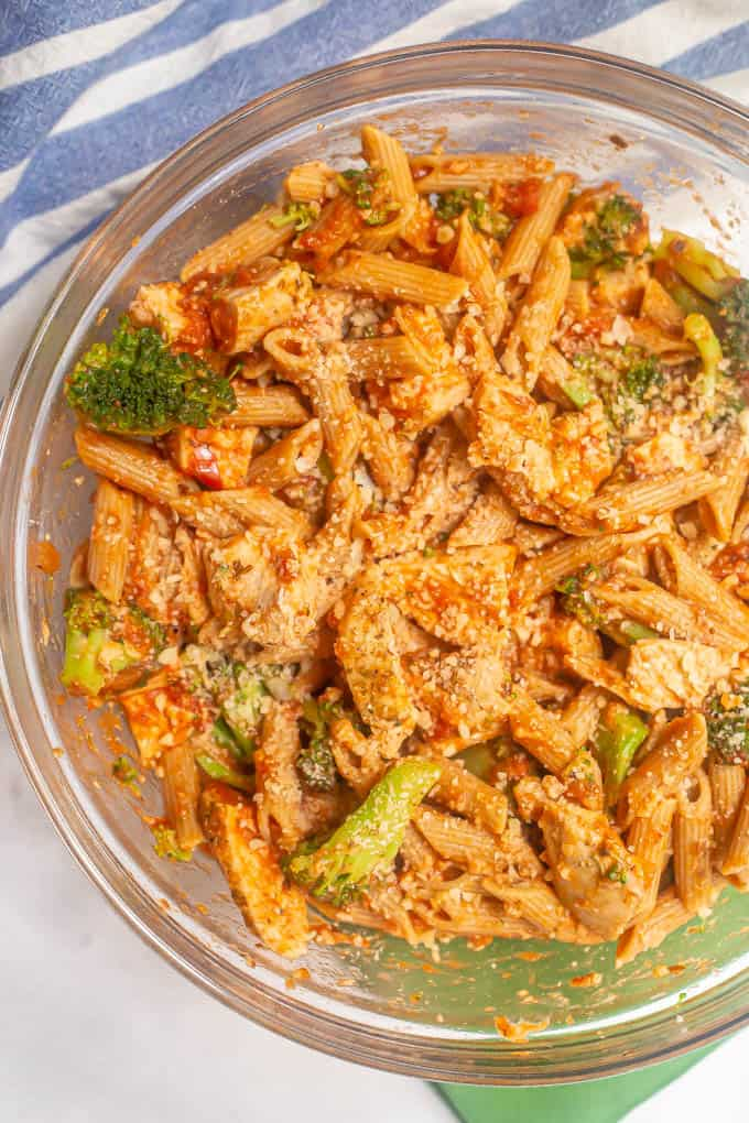 A glass mixing bowl with pasta, chicken and broccoli plus a tomato sauce