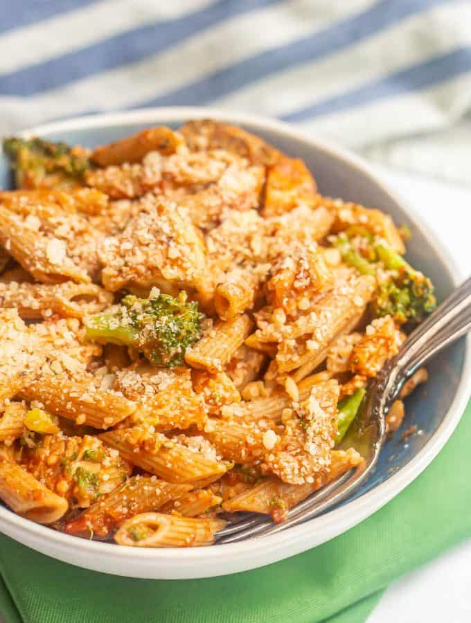 A large blue and white bowl with penne pasta, chicken and broccoli coated in marinara and Parmesan cheese