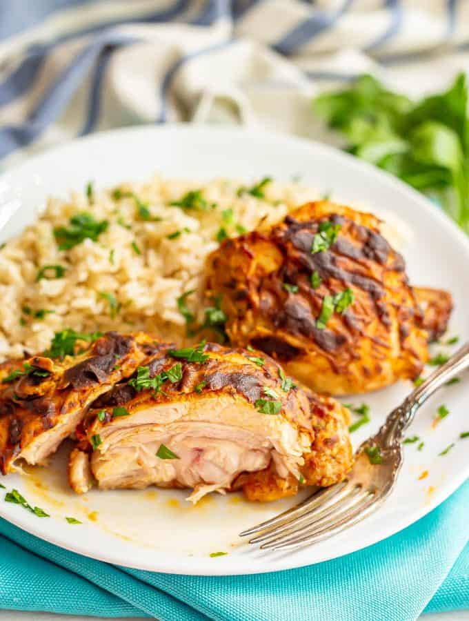 Sliced, cooked chicken thighs with Dijon mustard served on a white plate with rice