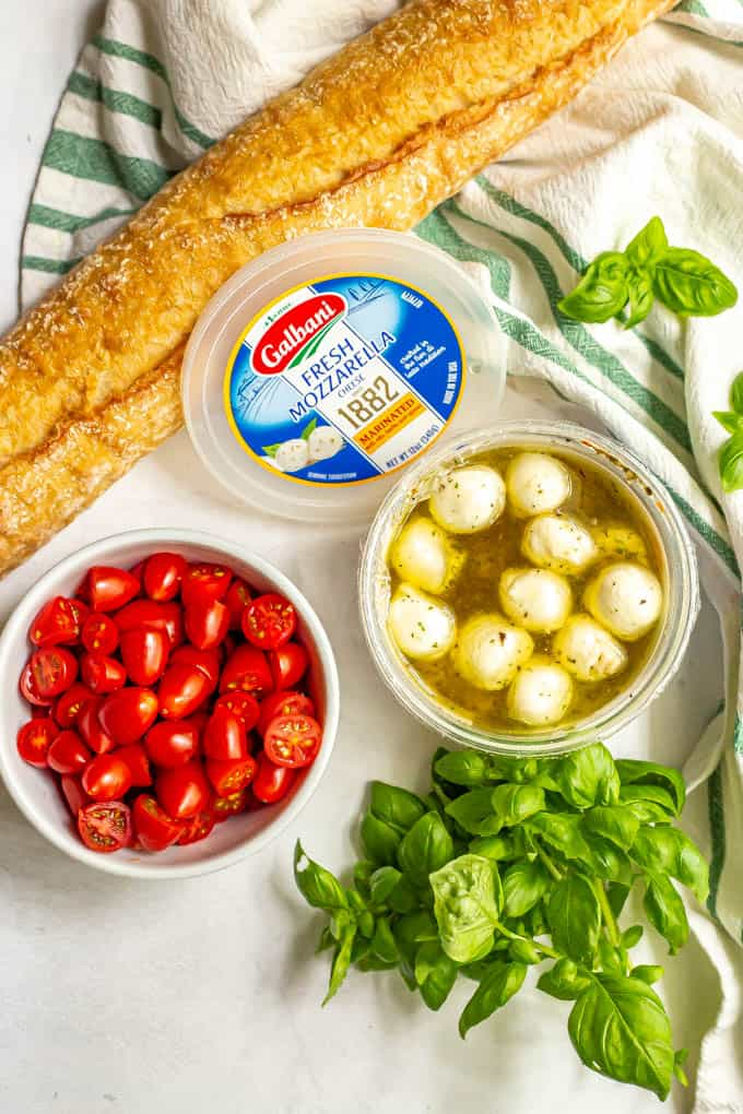 Ingredients laid out on a counter for making bruschetta, including a baguette, fresh tomatoes, marinated mozzarella and fresh basil
