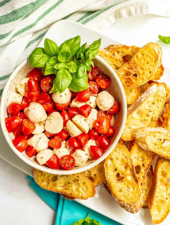 A bowl full of bruschetta toppings on a plate of toasted baguette slices