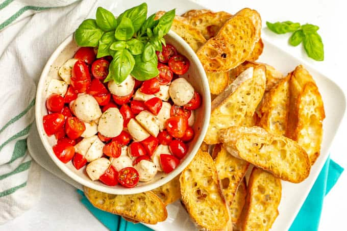 A serving platter of baguette slices with a bowl of marinated mozzarella with tomatoes and basil