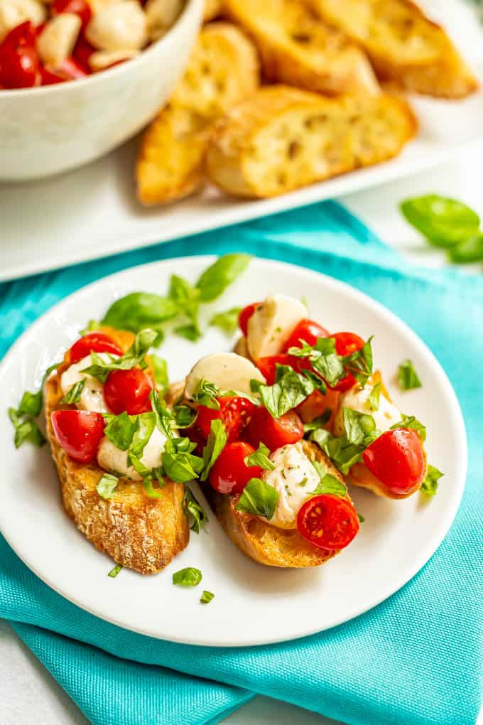 Bruschetta slices with tomatoes, mozzarella and basil on a small white plate