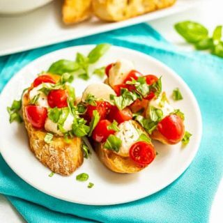 Baguette slices with tomatoes and mozzarella and basil on top