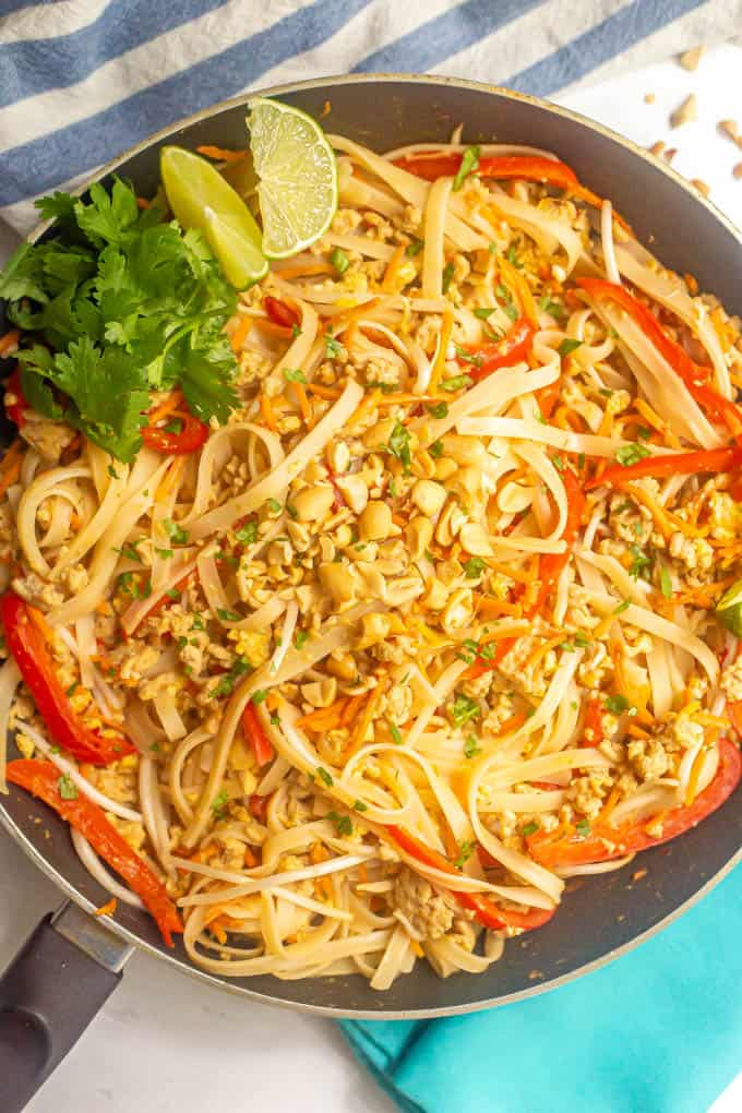 Chicken pad Thai with rice noodles in a large skillet topped with peanuts, cilantro and lime wedges