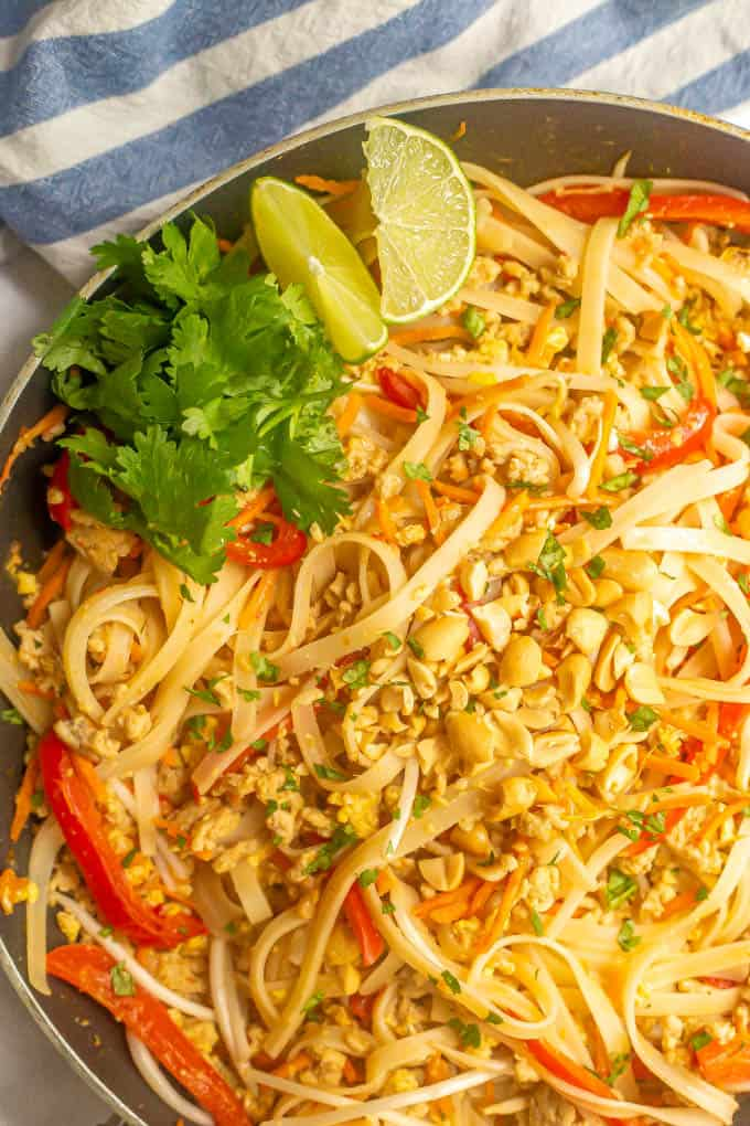 Close up of chicken pad Thai after its finished cooking in a skillet with cilantro sprigs and lime wedges on top