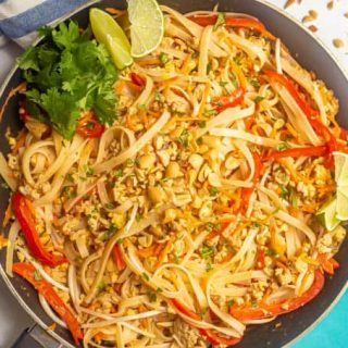 Finished dish of chicken pad Thai in a dark skillet with toppings scattered on top and nearby