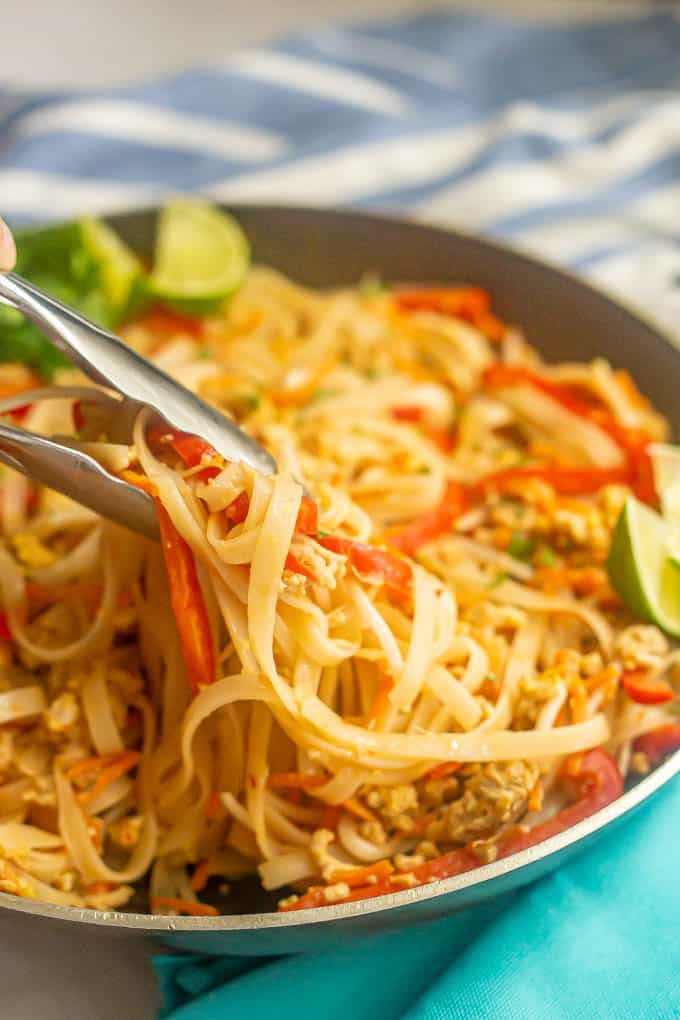 Tongs picking up a twirl of rice noodles with ground chicken and veggies from a large pan