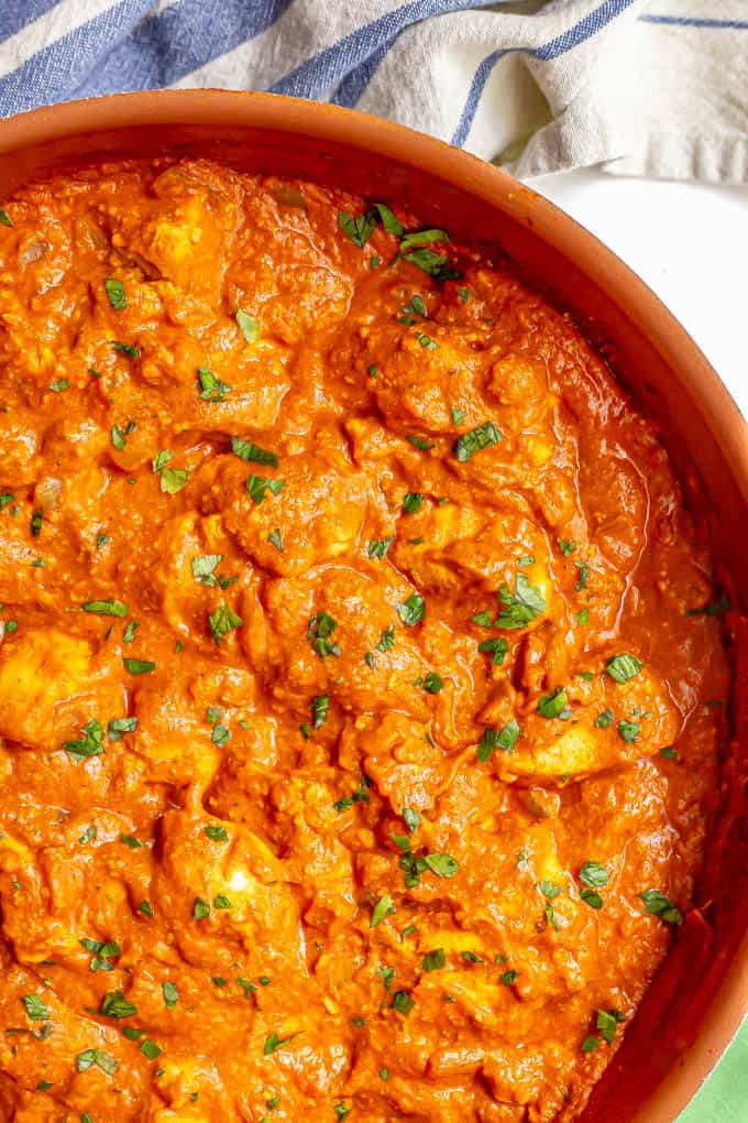 Close up of chicken tikka masala in a large skillet with a sprinkling of fresh parsley