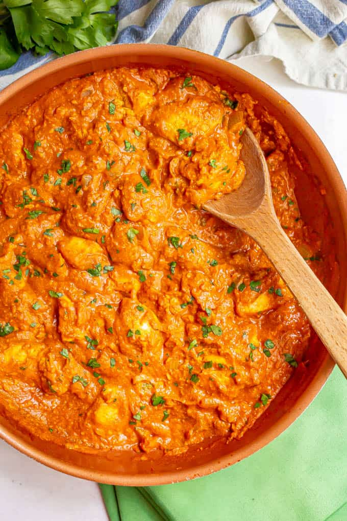 A large skillet with a wooden spoon picking up some chicken tikka masala