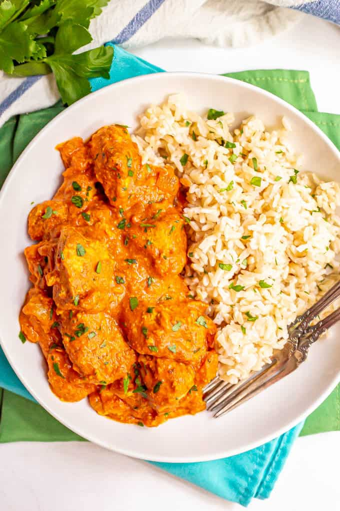 A plated serving of chicken tikka masala alongside steamed brown rice and chopped parsley