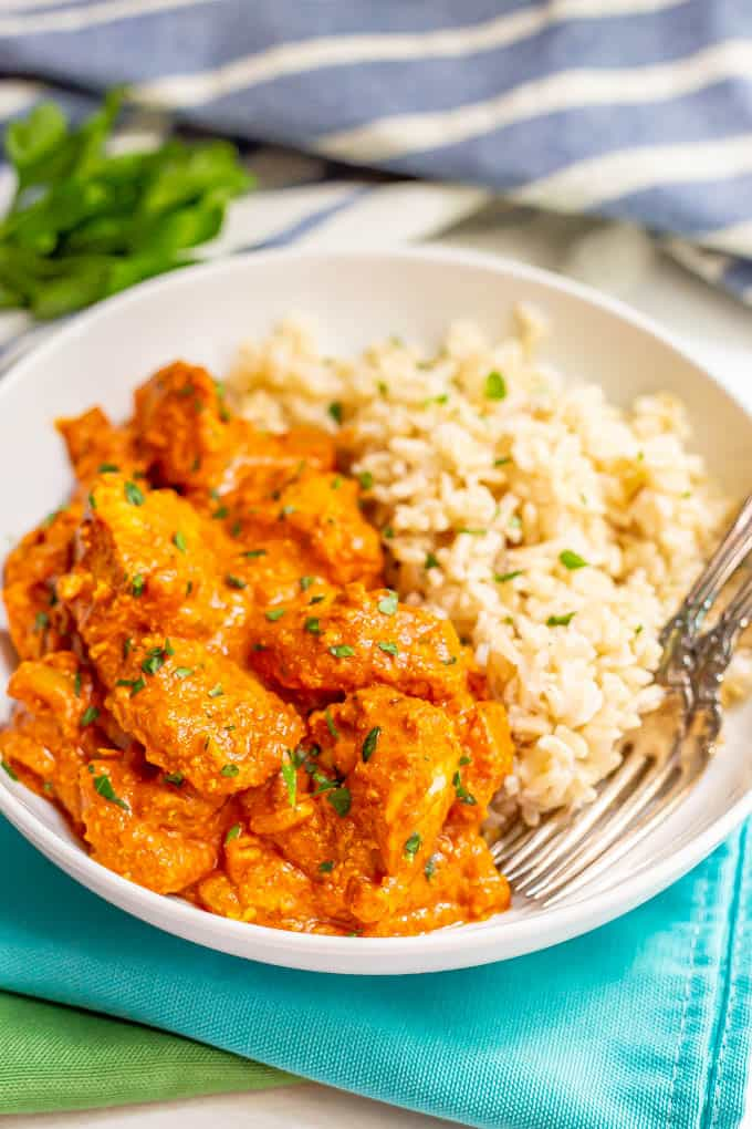 A plated serving of chicken tikka masala alongside steamed brown rice with two forks