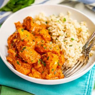 A plated serving of chicken tikka masala alongside steamed brown rice with two forks alongside