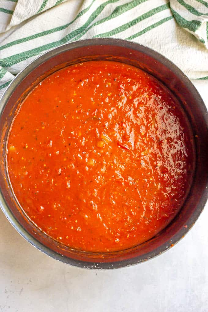 A large black pot of tomato soup before being pureed