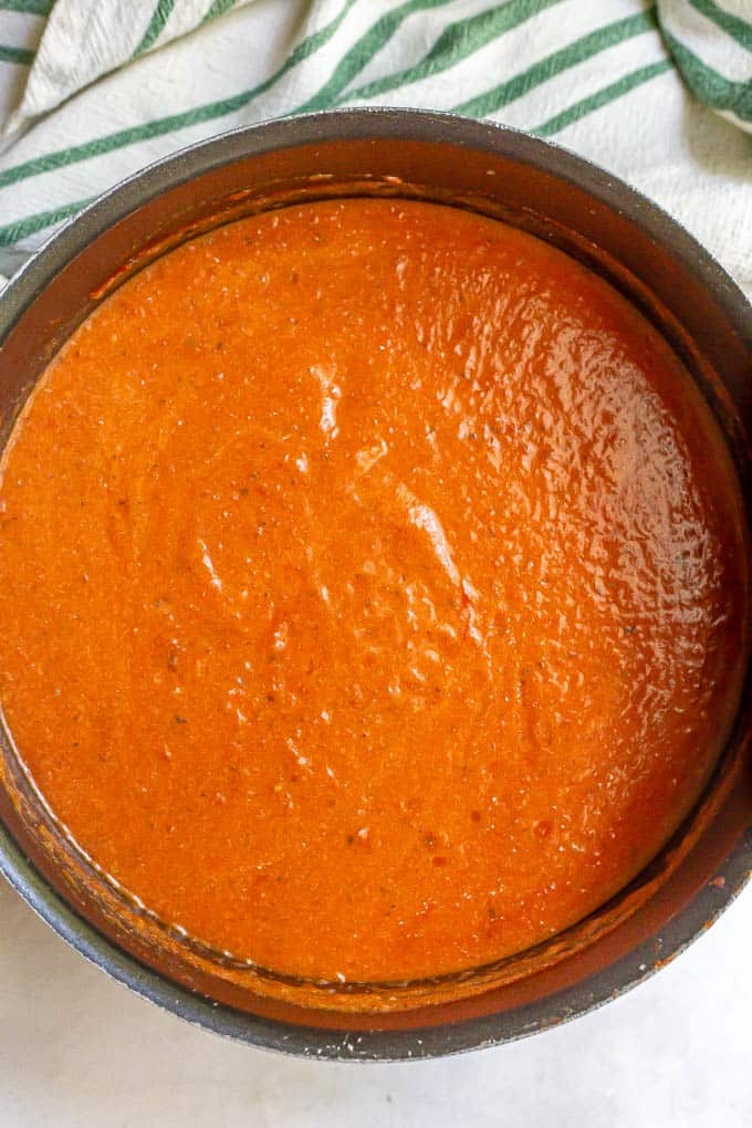 A large black pot of creamy tomato soup after being pureed