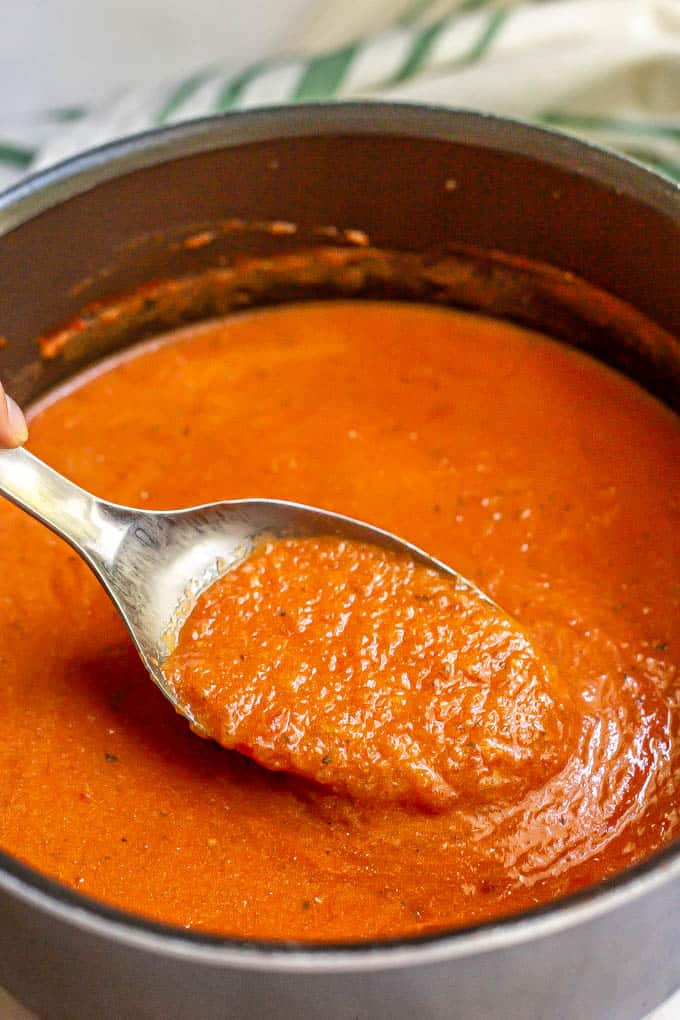 A serving spoon lifting a scoop of tomato soup from a large pot