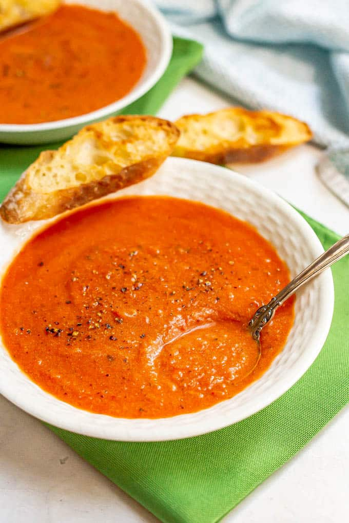 A spoon resting in a bowl of creamy tomato soup with a toasted slice of bread resting on the side of the bowl