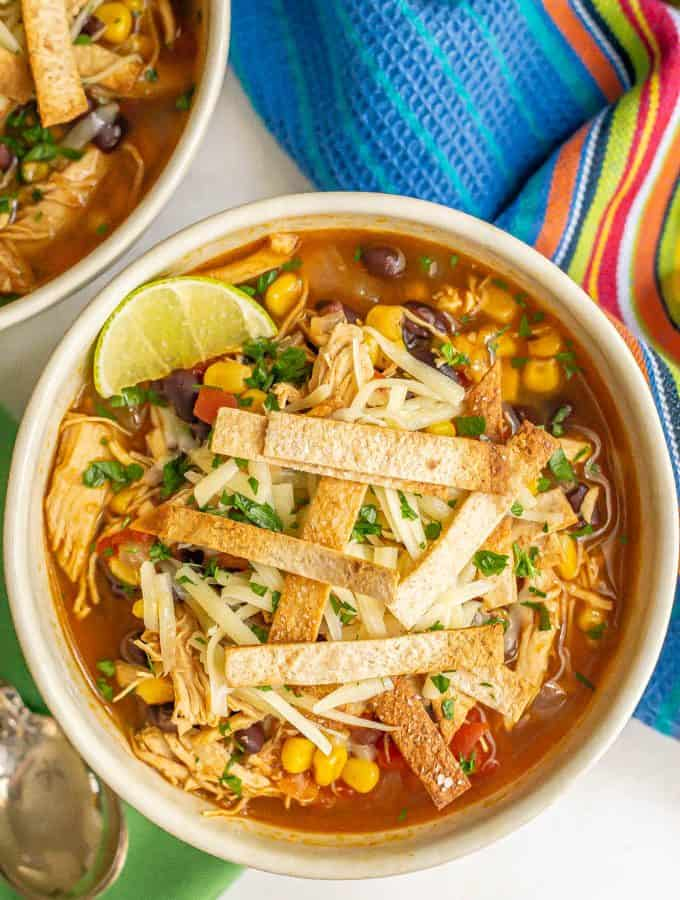 A bowl of chicken tortilla soup with black beans and corn, topped with tortilla strips, cheese and a lime wedge