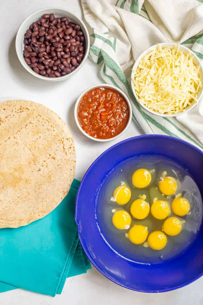 Breakfast burrito ingredients in separate bowls on a white marble counter